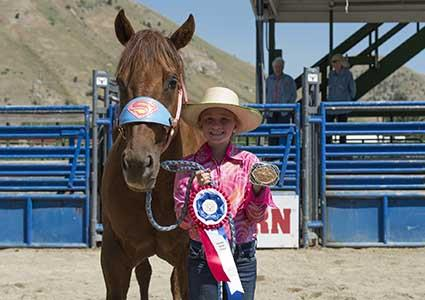 A girl standing next to her horse with an award.