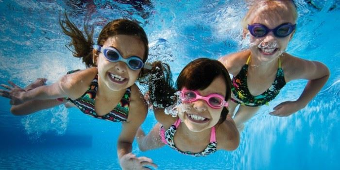 Three kids swimming under water with goggles on.