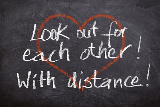 """Look out for each other - with distance!"" written on a chalkboard"